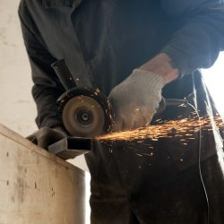 Close Up Of Cutting Metal Pipe, Man Using Angle Grinder. Hot work permits.