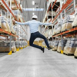 Happy Businessman In Helmet Jumping At Warehouse